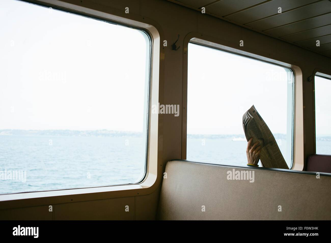 Mans hand holding up newspaper on seat on passenger ferry - Stock Image