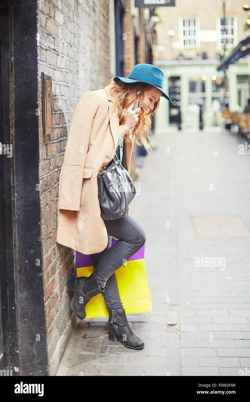 Stylish young female shopper chatting on smartphone, London, UK - Stock Image