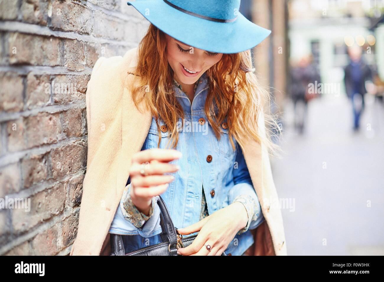 Stylish young female shopper fastening handbag, London, UK - Stock Image
