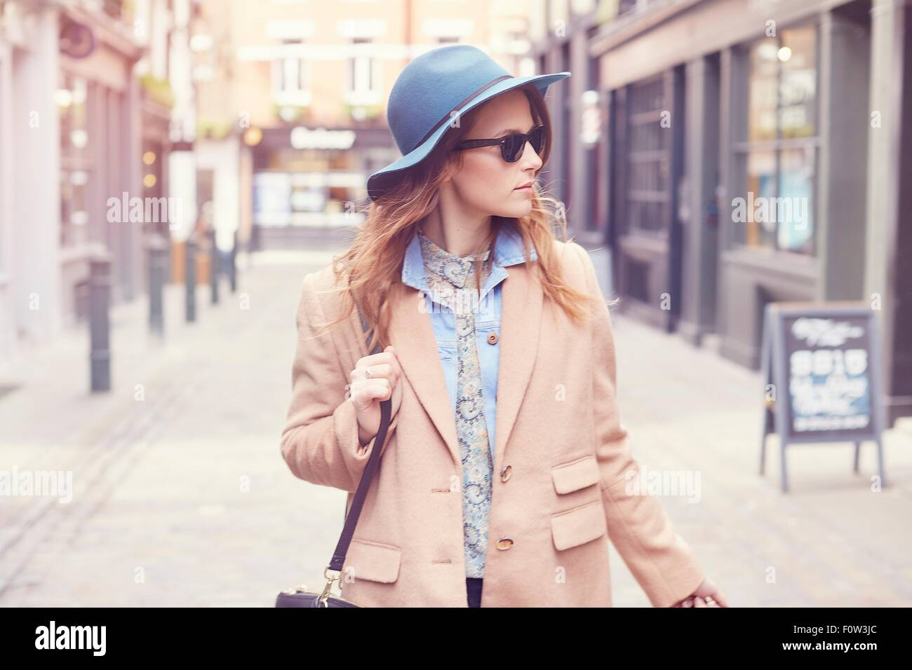 Stylish young female shopper strolling on street, London, UK - Stock Image