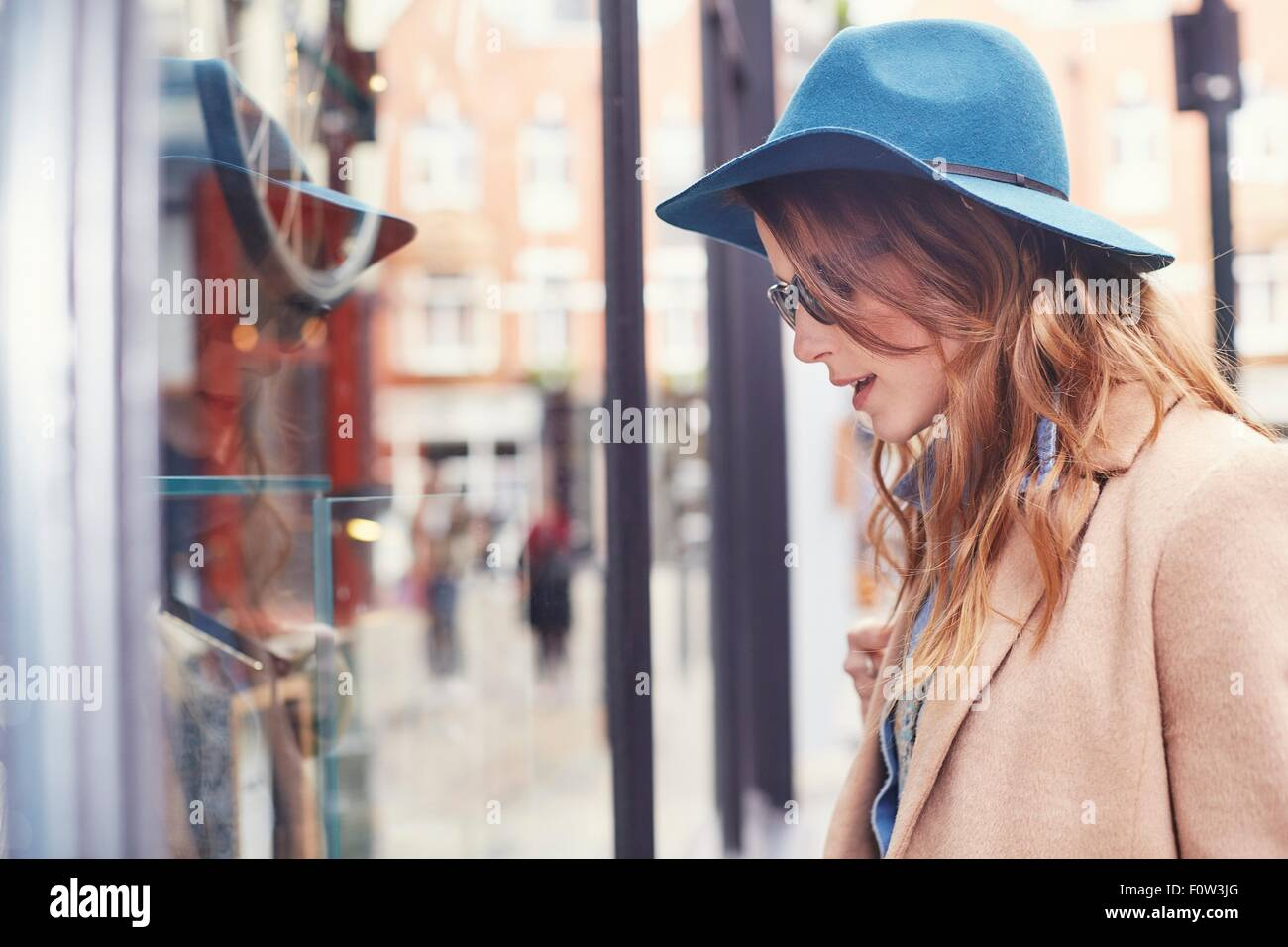 Stylish young female shopper looking at shop window, London, UK - Stock Image
