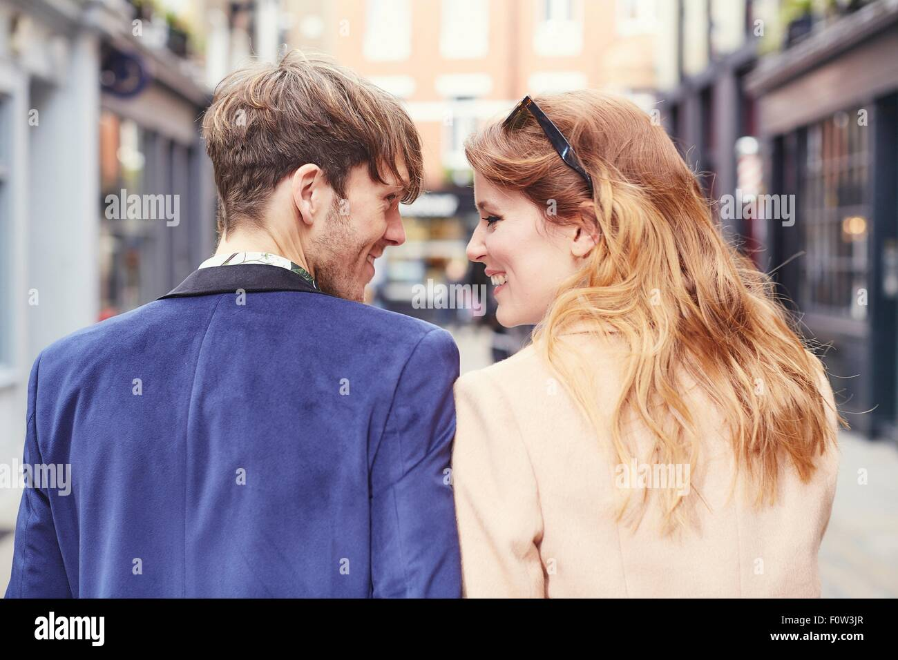 Rear view of couple strolling along street, London, UK - Stock Image