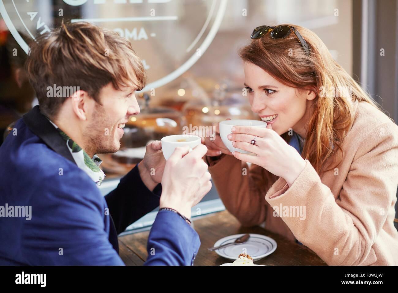 Couple drinking coffee at sidewalk cafe, London, UK - Stock Image