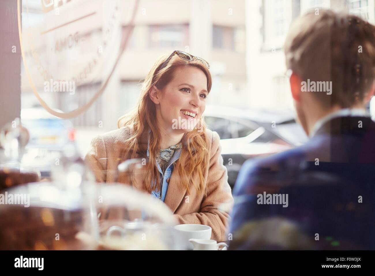 Couple chatting at sidewalk cafe, London, UK - Stock Image