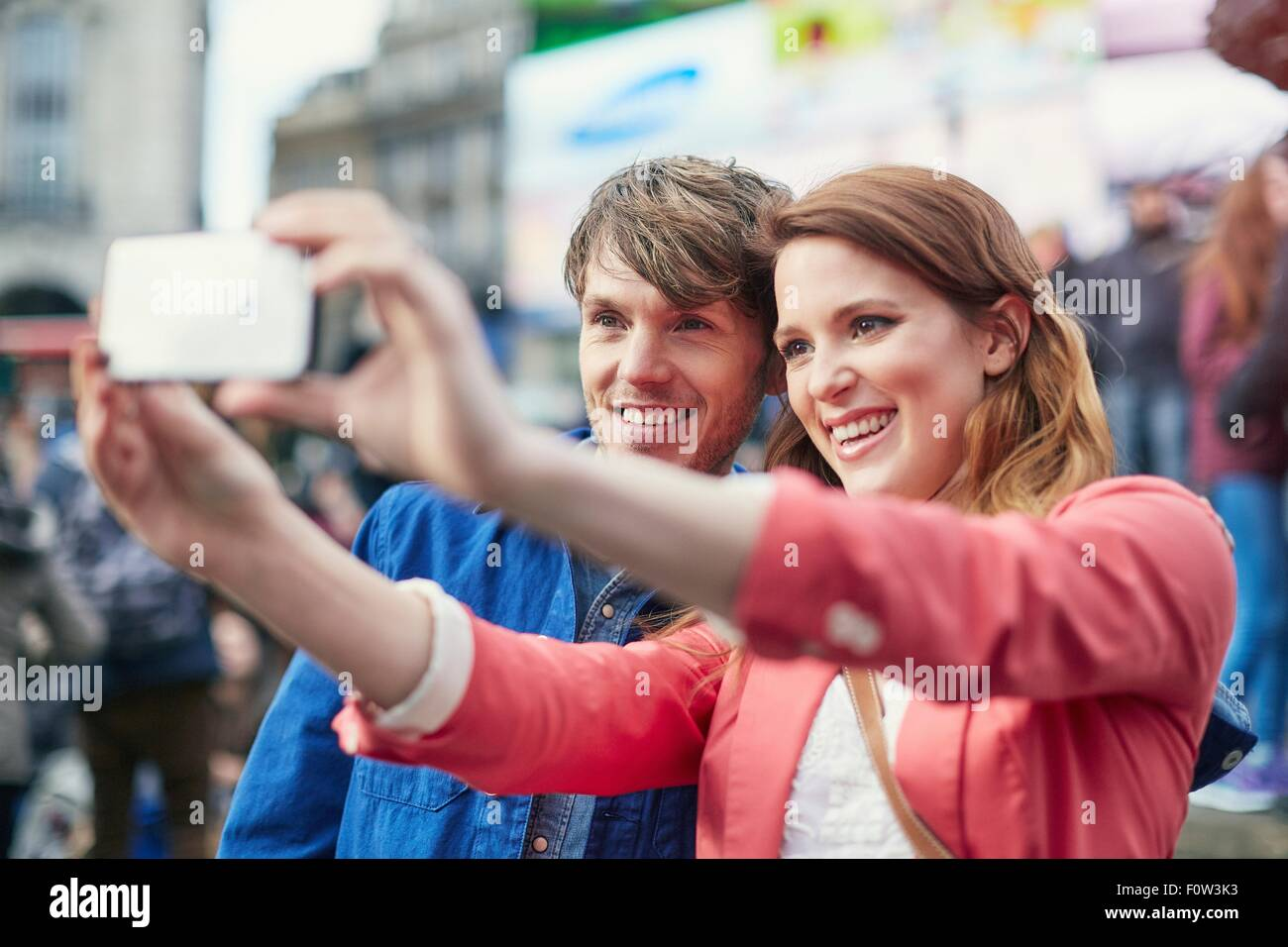 Tourist couple taking smartphone selfie at Piccadilly Circus, London, UK - Stock Image