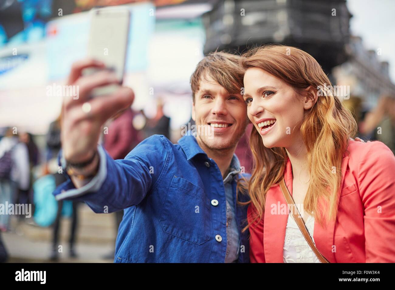 Tourist couple taking selfie on smartphone at Piccadilly Circus, London, UK - Stock Image