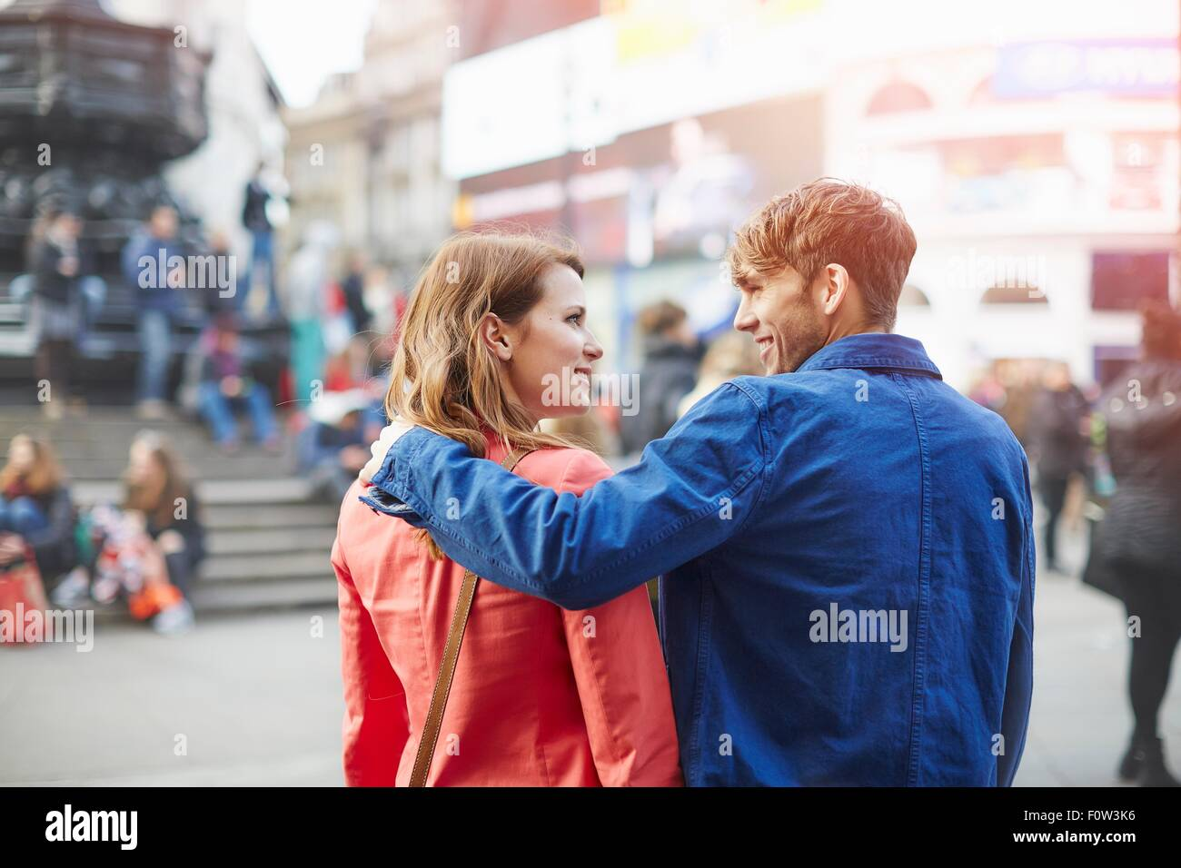 Tourist couple strolling at Piccadilly Circus, London, UK - Stock Image