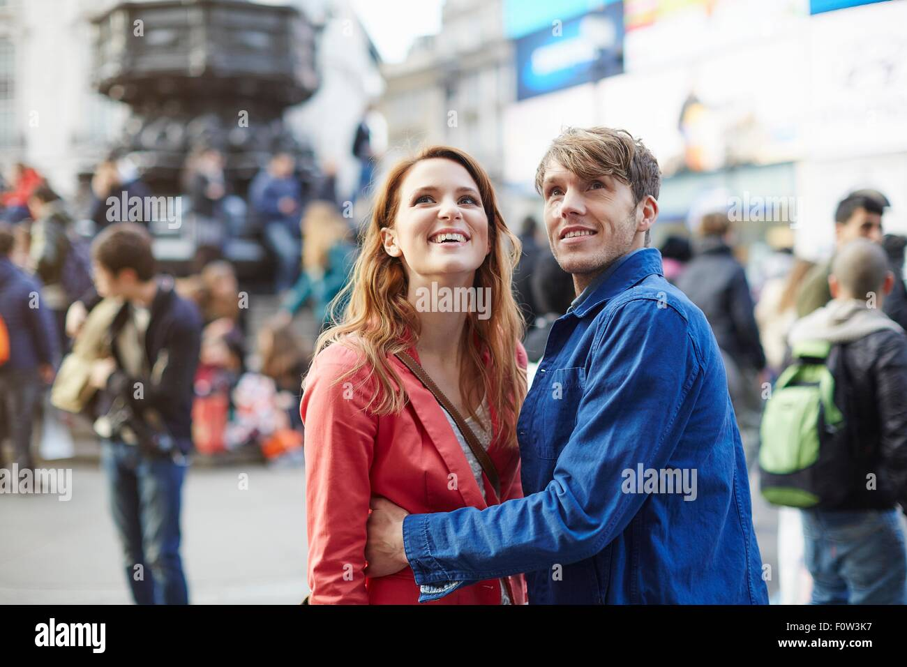 Tourist couple looking up from Piccadilly Circus, London, UK - Stock Image