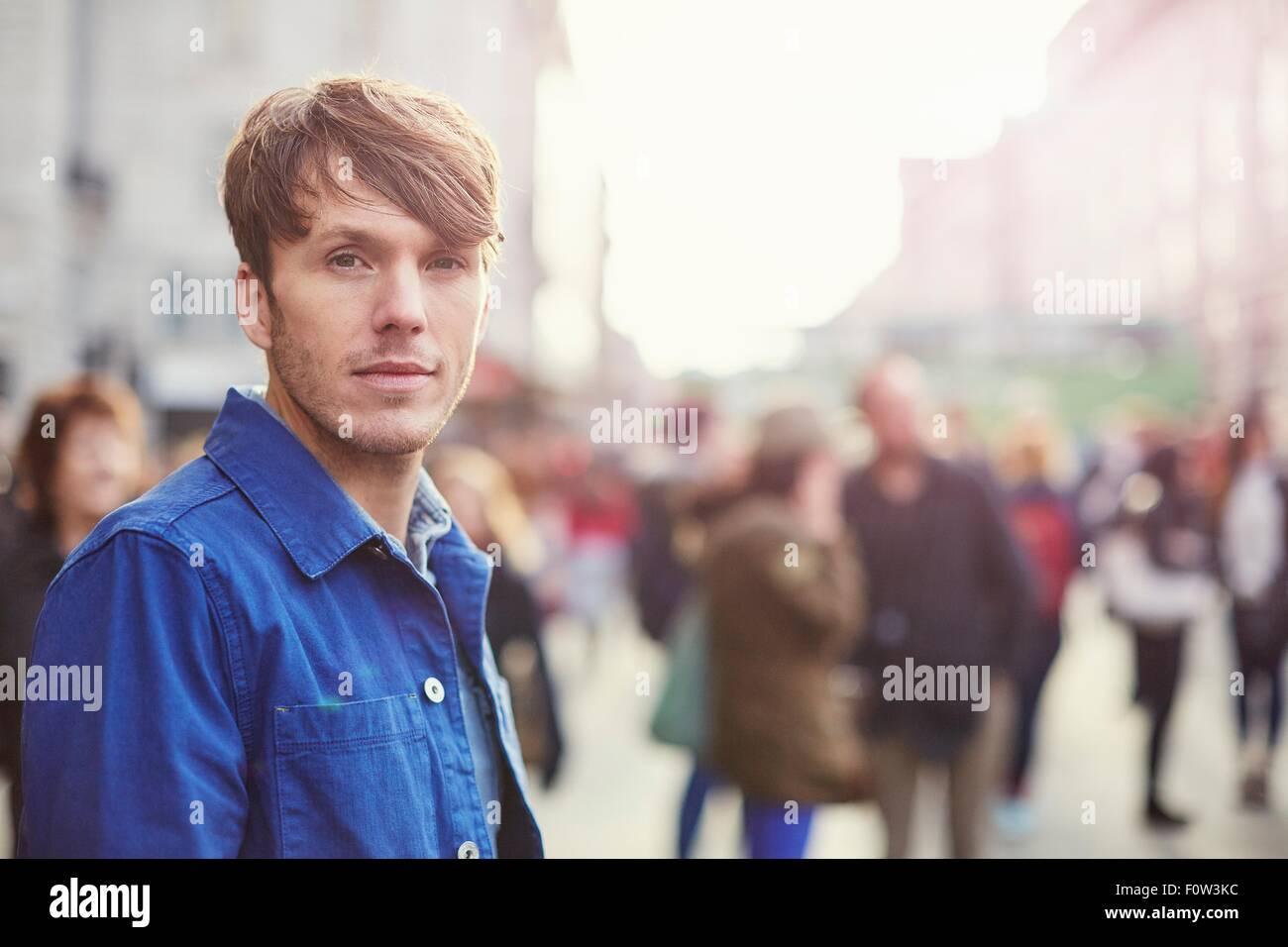 Portrait of mid adult man on crowded street, London, UK - Stock Image