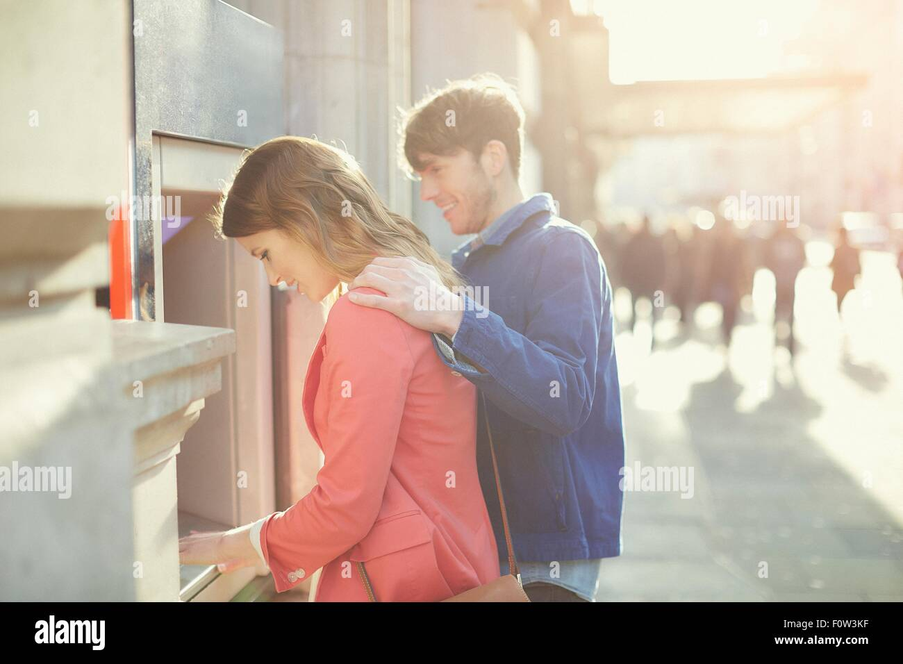 Couple withdrawing money from cash machine on street, London, UK - Stock Image