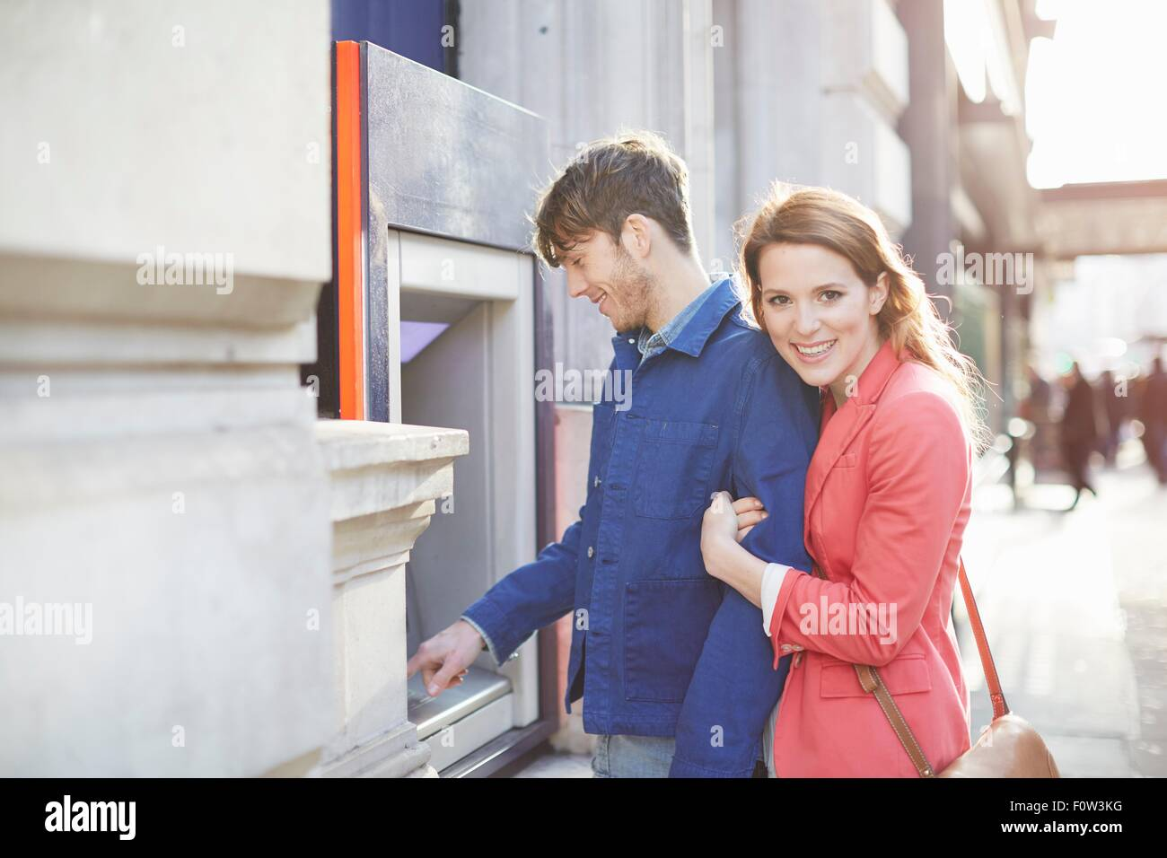 Couple withdrawing money from street cash machine, London, UK - Stock Image