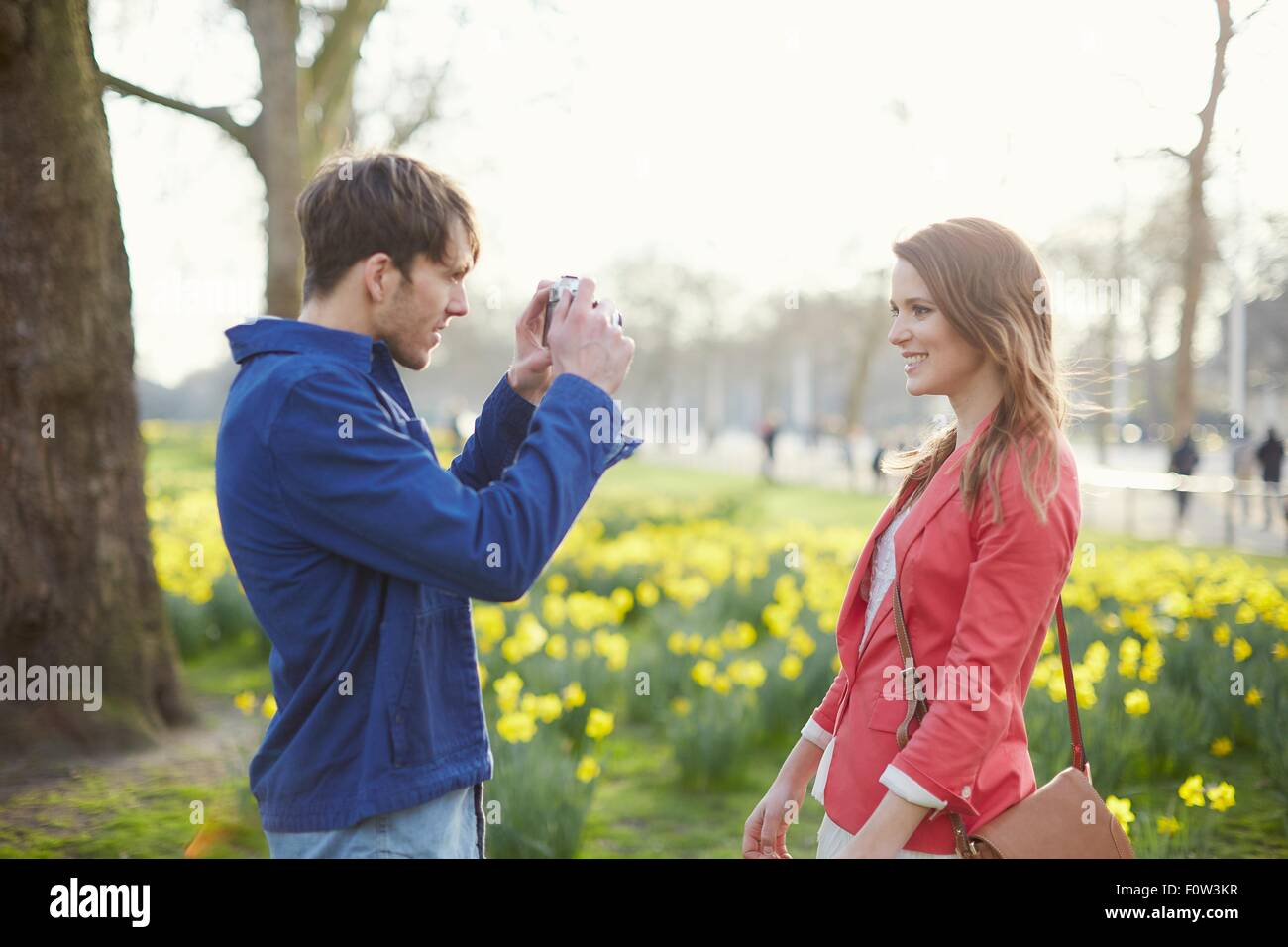 Mid adult man photographing girlfriend in park, London, UK - Stock Image
