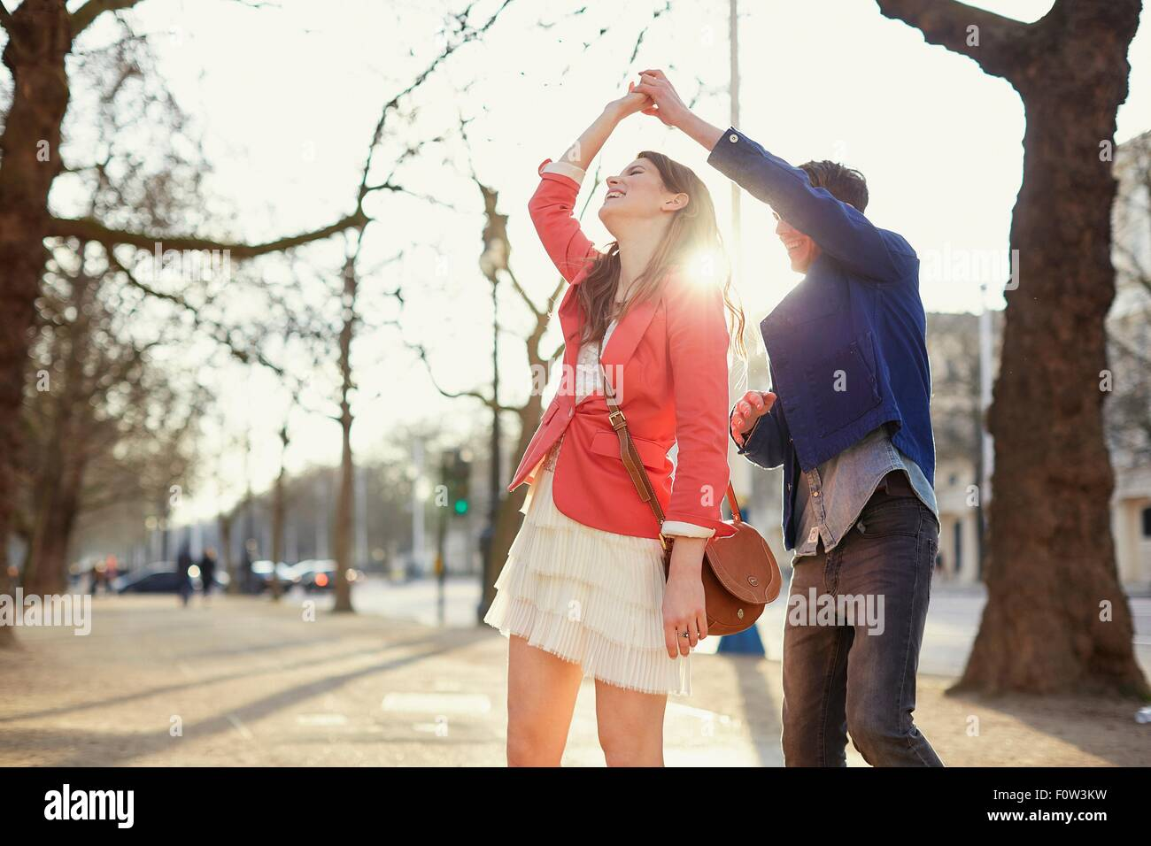 Romantic couple twirling in sunlit park, London, UK - Stock Image