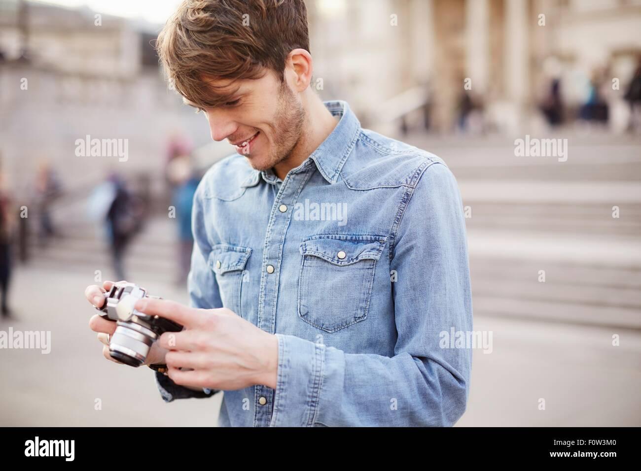 Mid adult man reviewing camera photographs, Trafalgar Square fountain, London, UK - Stock Image