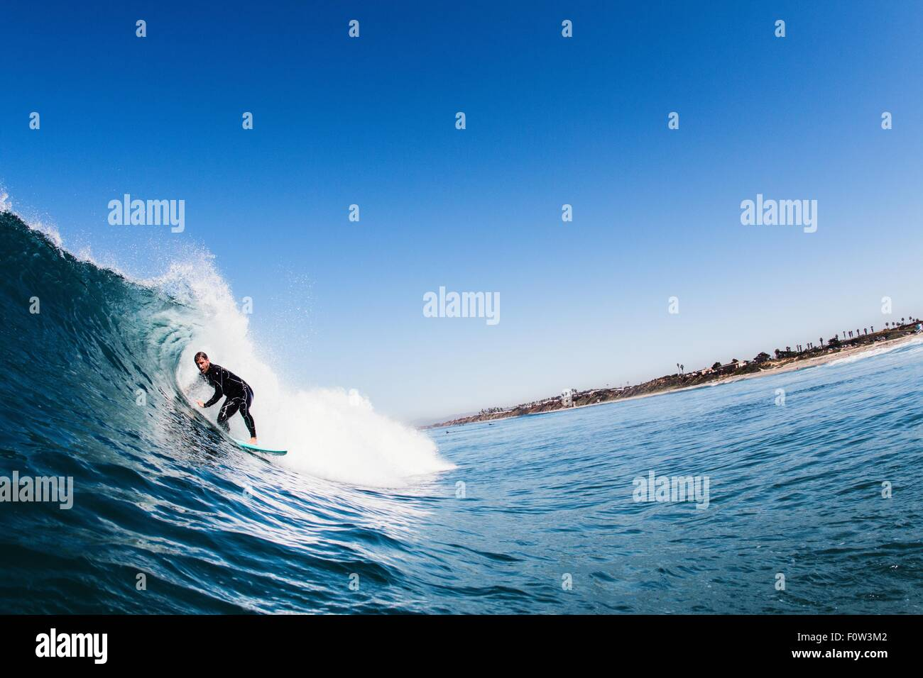 Mid adult male surfer surfing curved wave, Carlsbad, California, USA - Stock Image