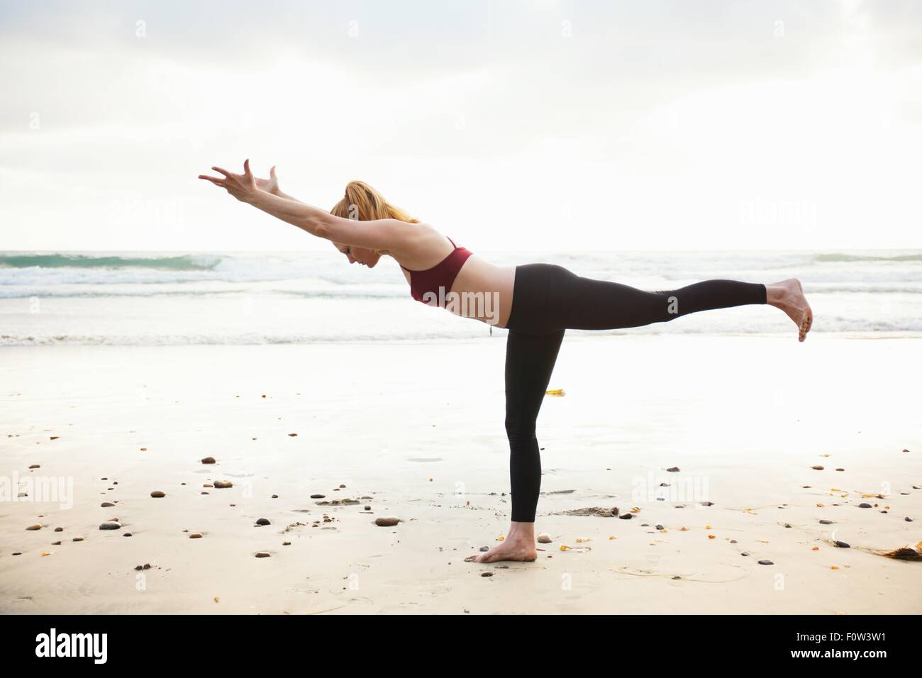 Mid adult woman practicing warrior yoga pose on beach - Stock Image