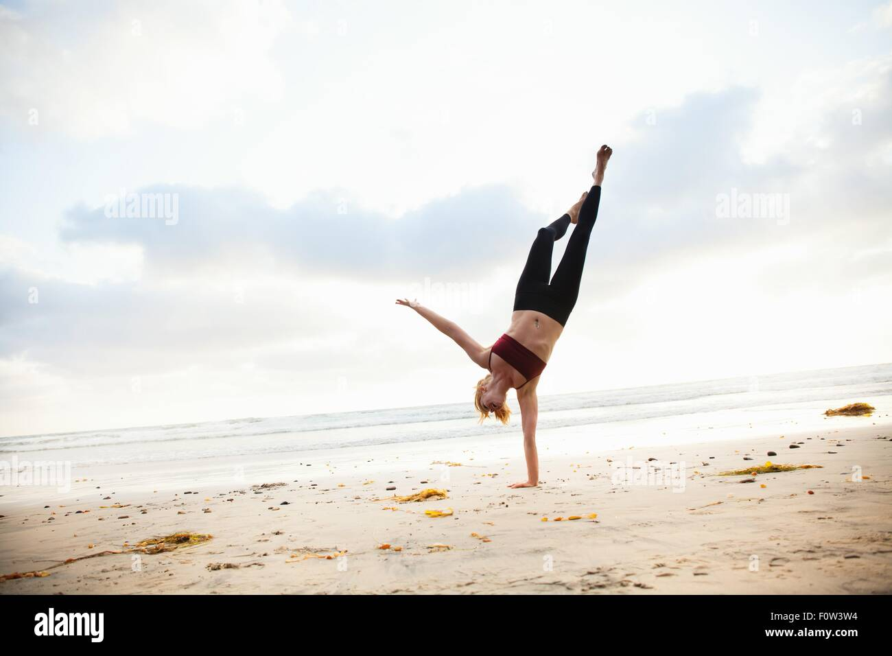 Mid adult woman practicing yoga position on beach - Stock Image