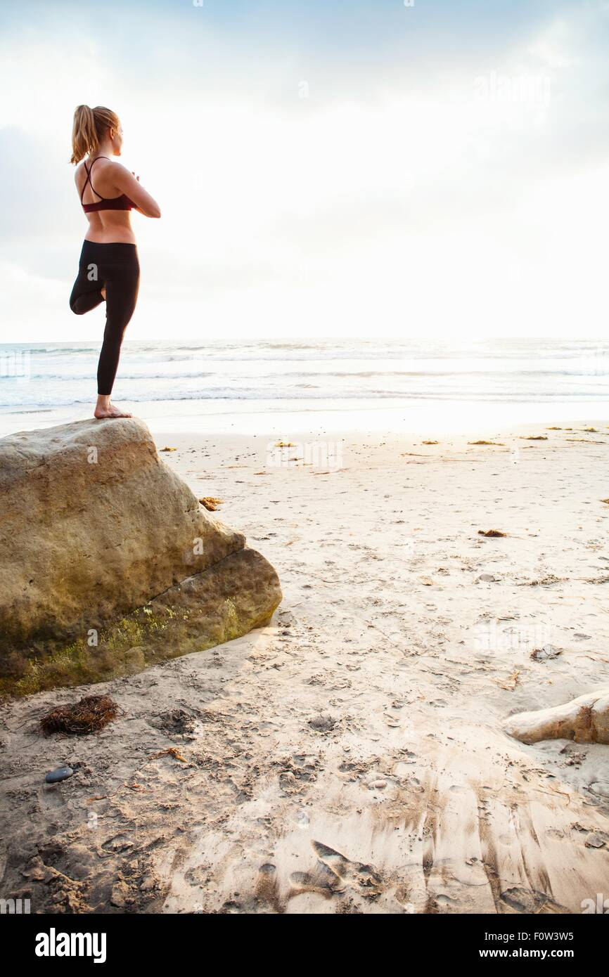 Mid adult woman practicing tree yoga pose on beach rock - Stock Image