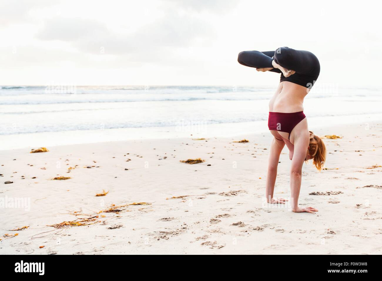 Mid adult woman upside down in yoga position on beach - Stock Image