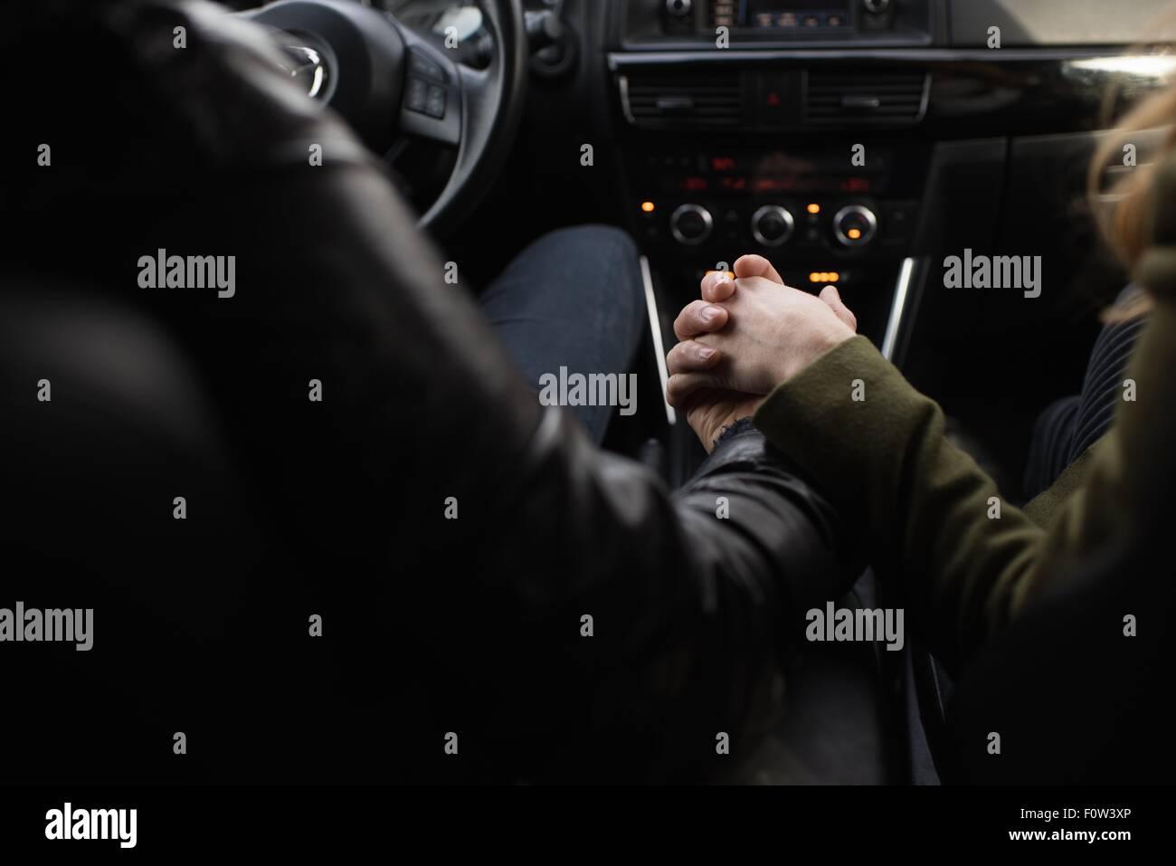 Couple holding hands inside vehicle - Stock Image