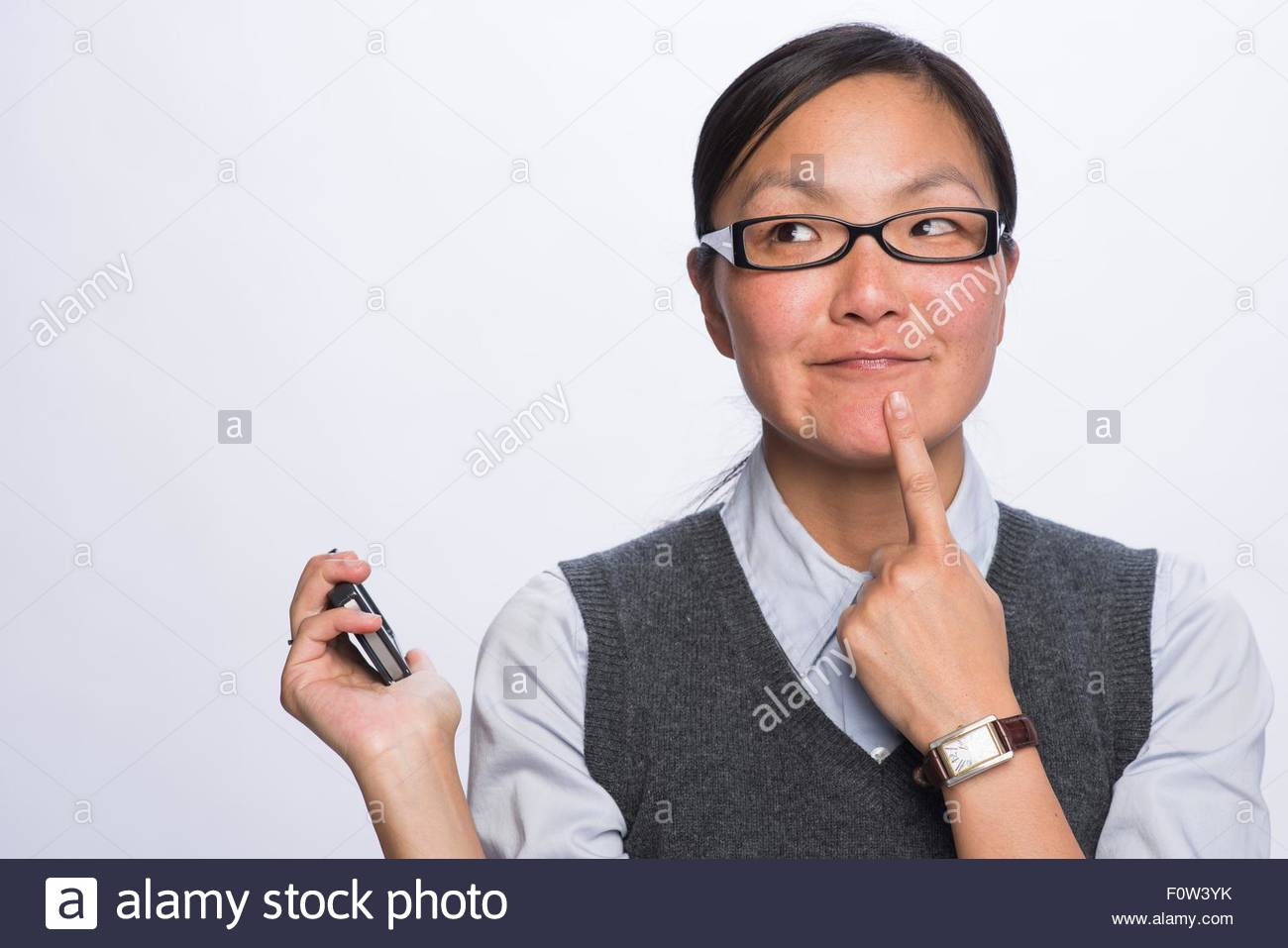 Businesswoman with smartphone resting finger on chin - Stock Image