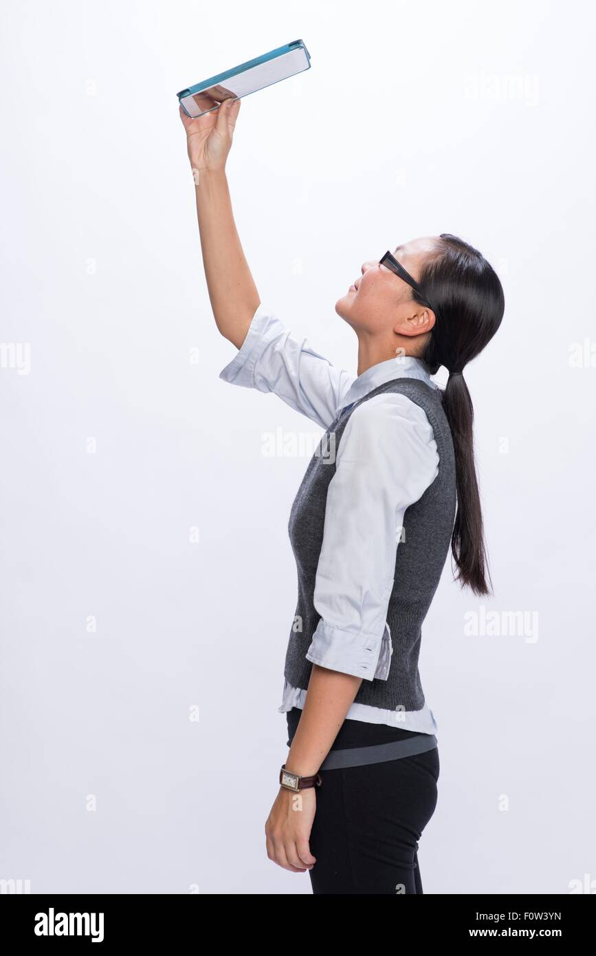 Businesswoman looking upwards at digital tablet - Stock Image