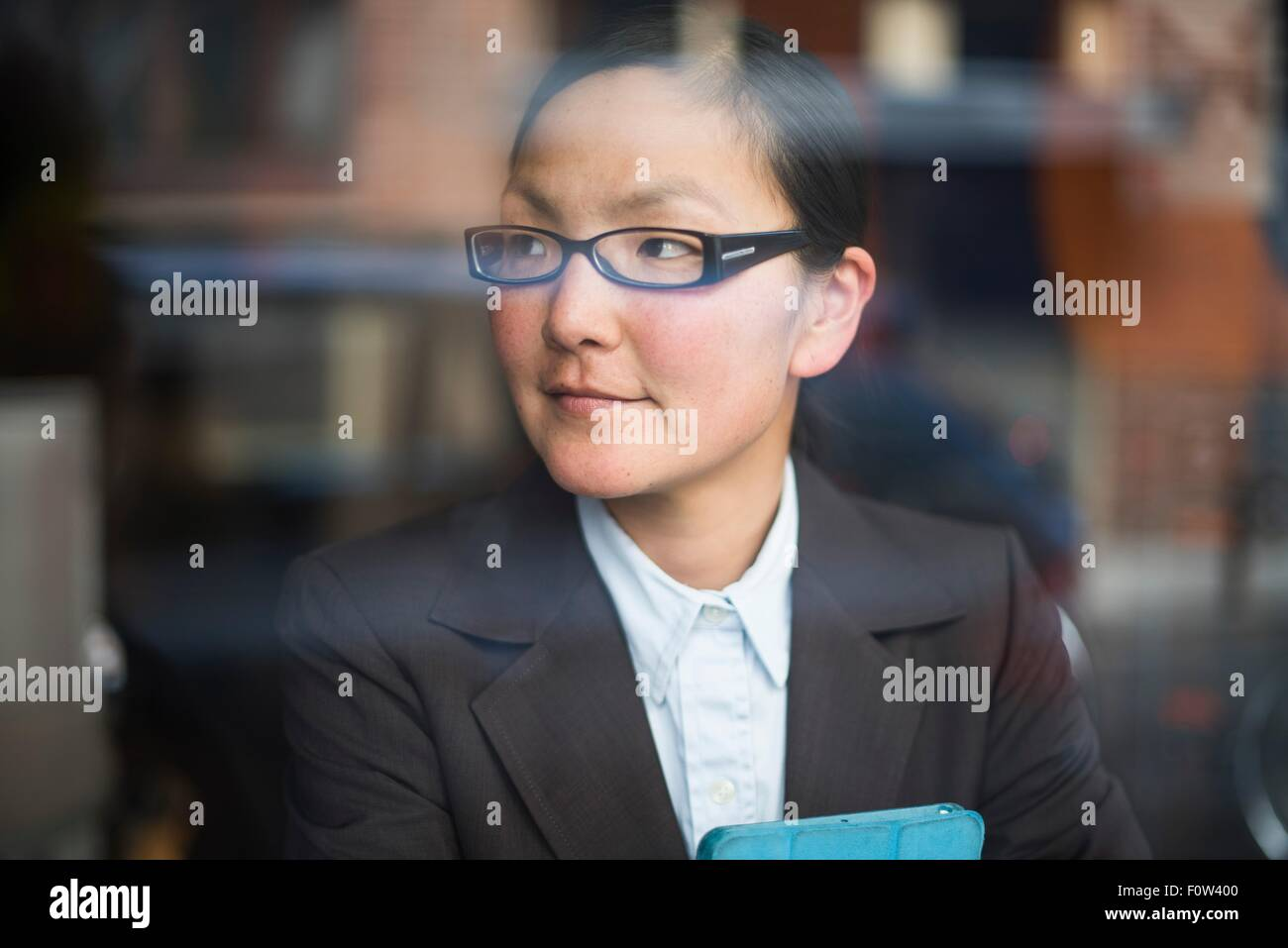 Businesswoman with digital tablet, behind glass window - Stock Image