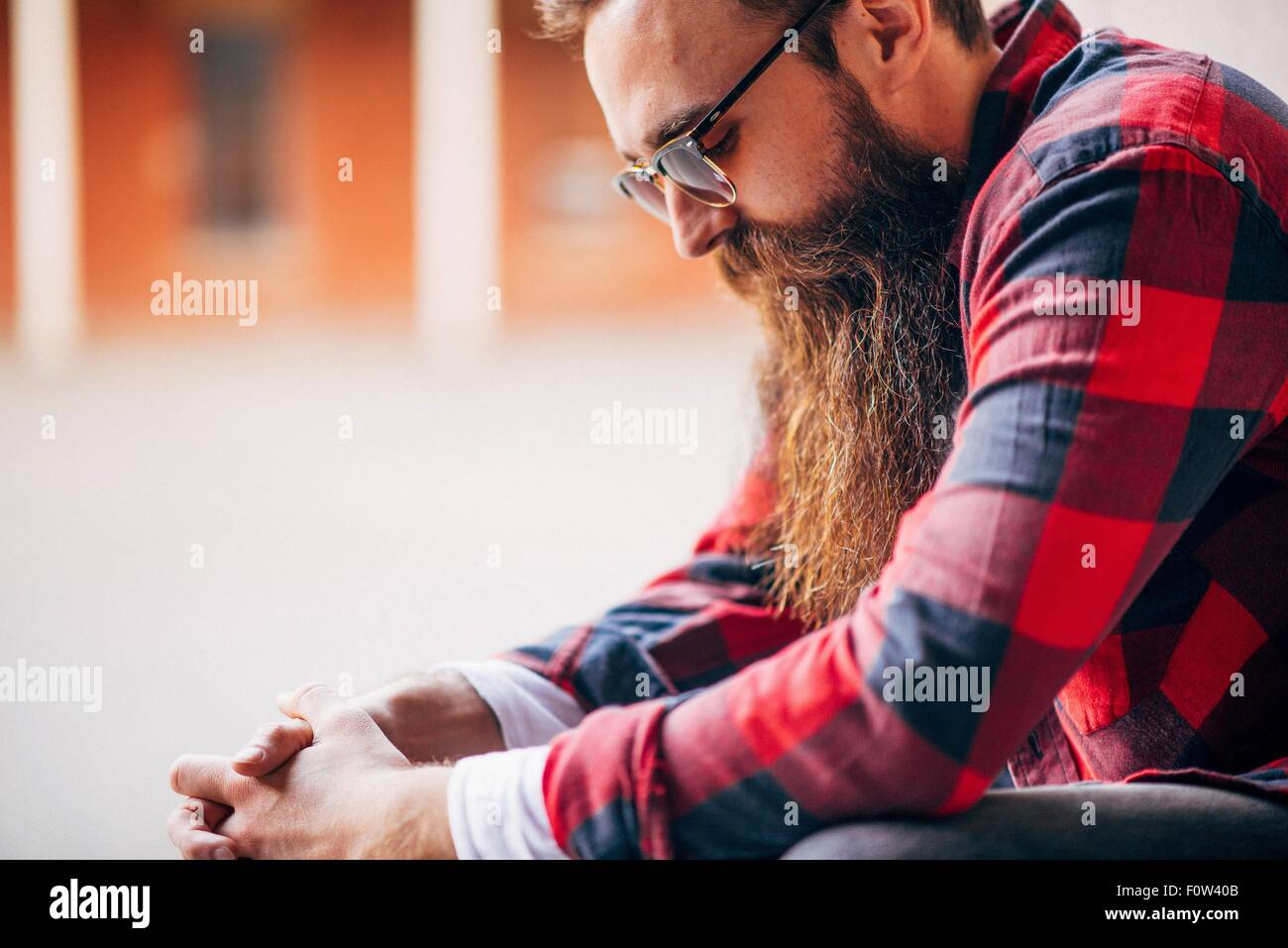 Side view of man with beard wearing sunglasses looking down - Stock Image