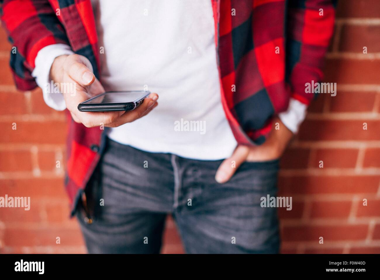 Detail shot of man's hands holding smartphone - Stock Image