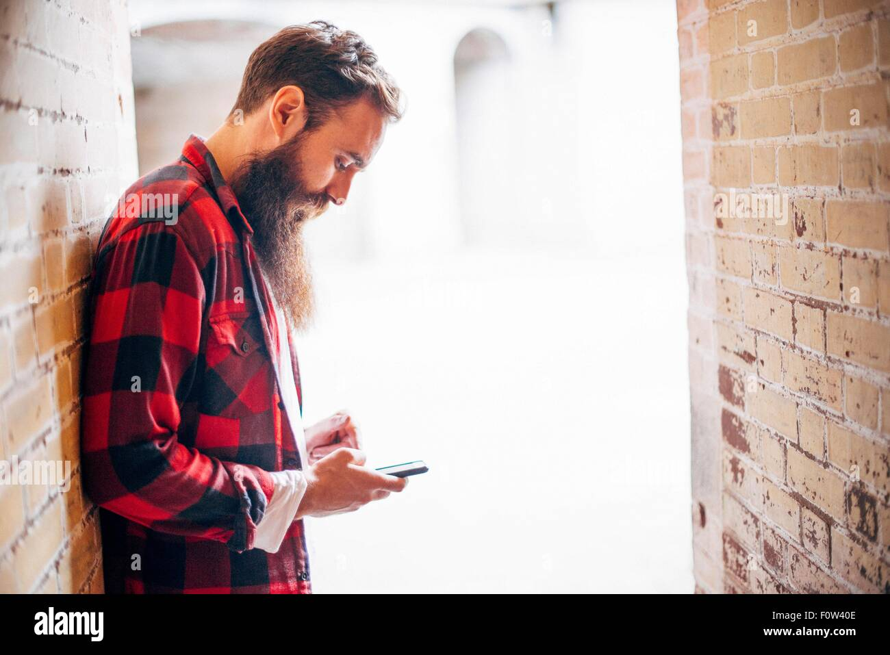 Side view of man with beard holding smartphone - Stock Image
