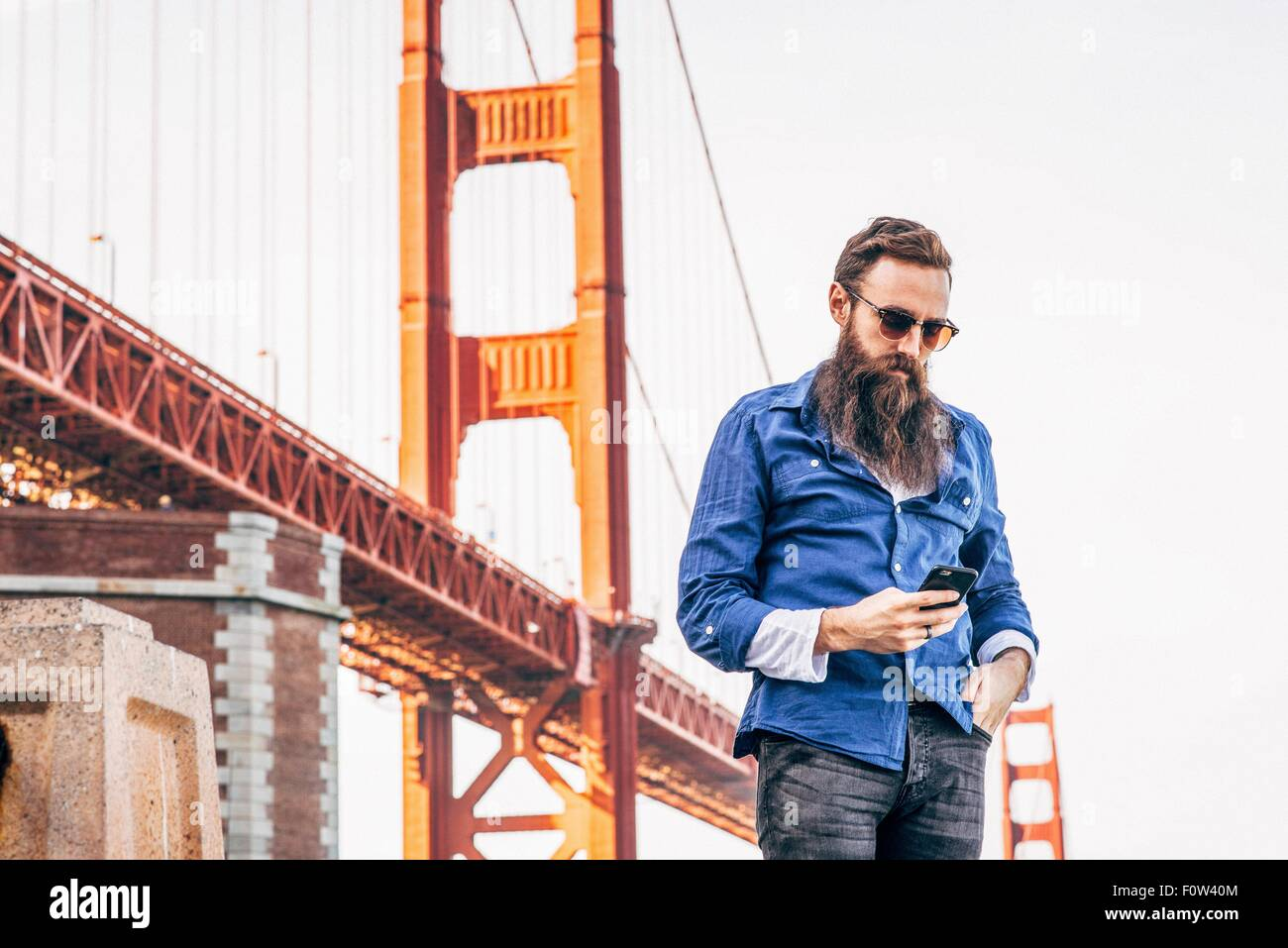 Man with beard checking smartphone at Golden Gate Bridge, San Francisco, California, USA - Stock Image