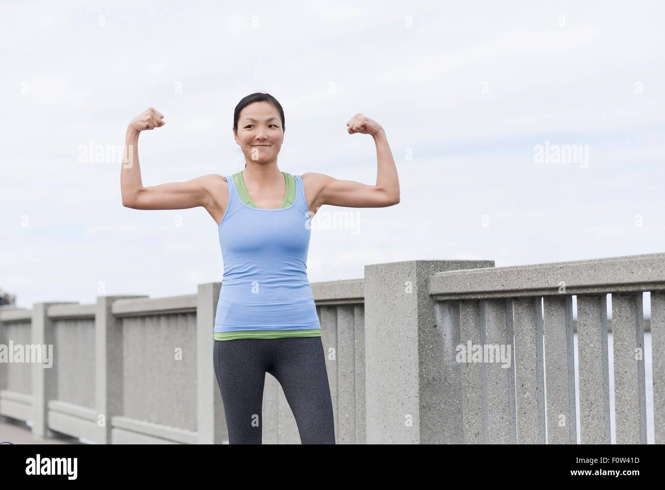 Female runner flexing muscles on bridge, San Francisco, California - Stock Image