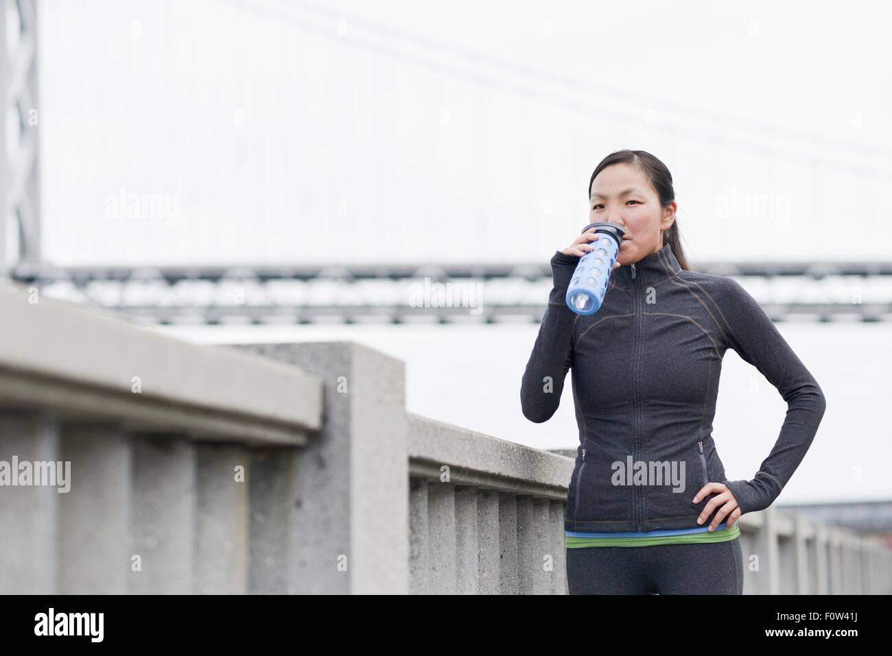 Female runner drinking on bridge, San Francisco, California Stock Photo