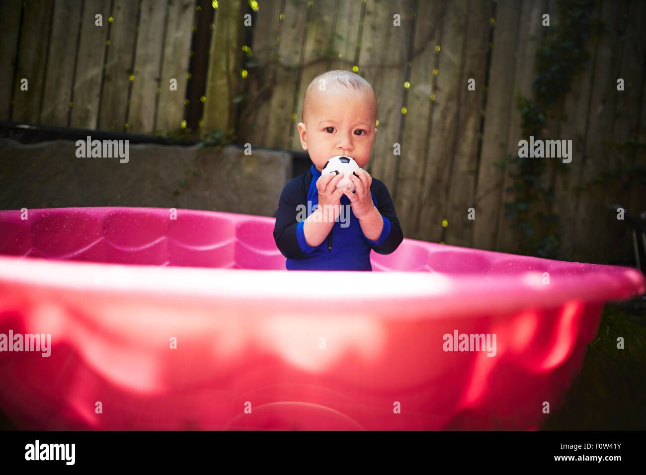 Baby boy inside pink tub - Stock Image