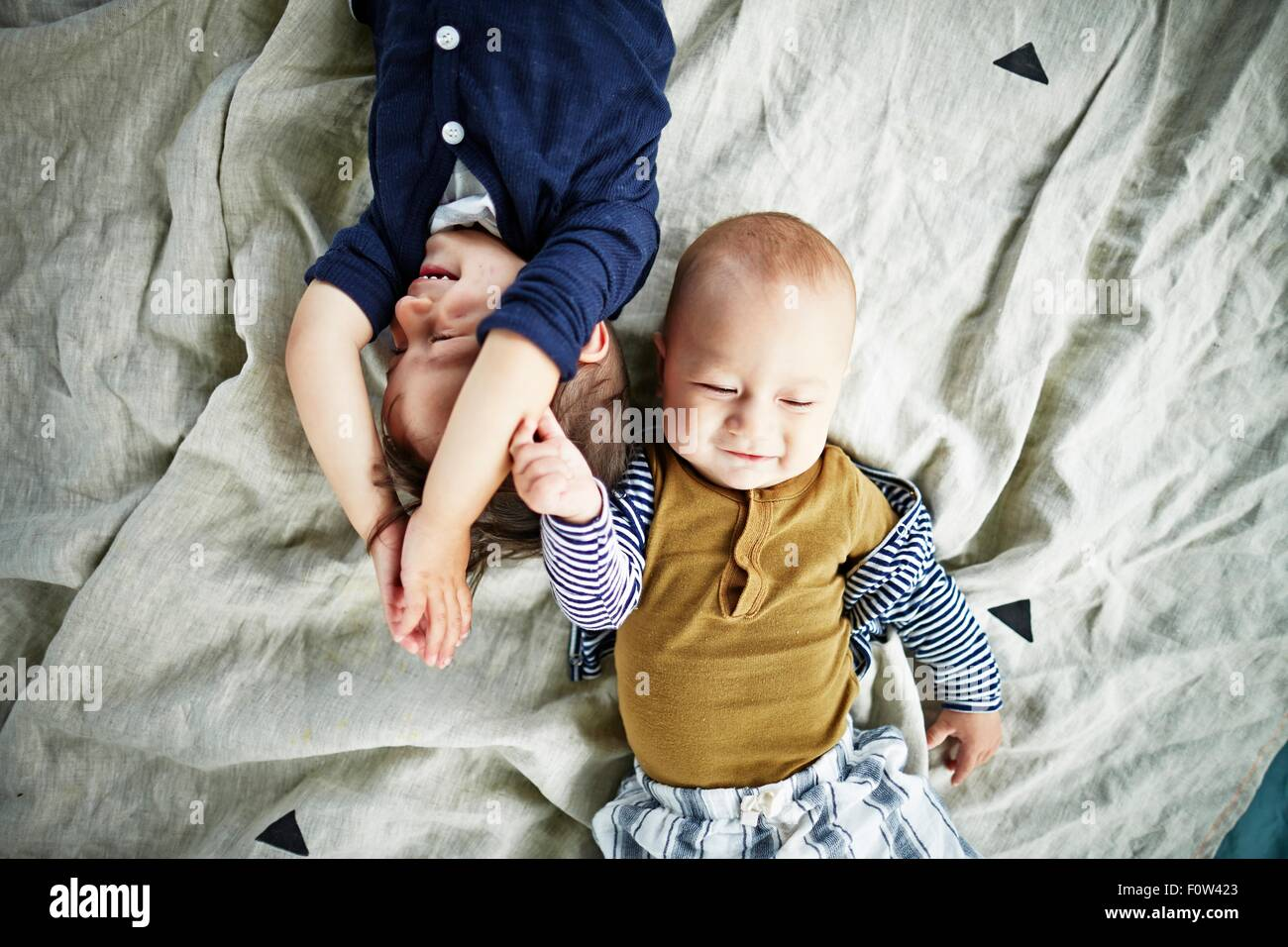 Brothers playing on bed - Stock Image