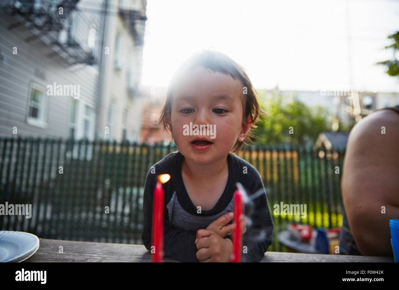 Boy looking at lit candle on dining table - Stock Image