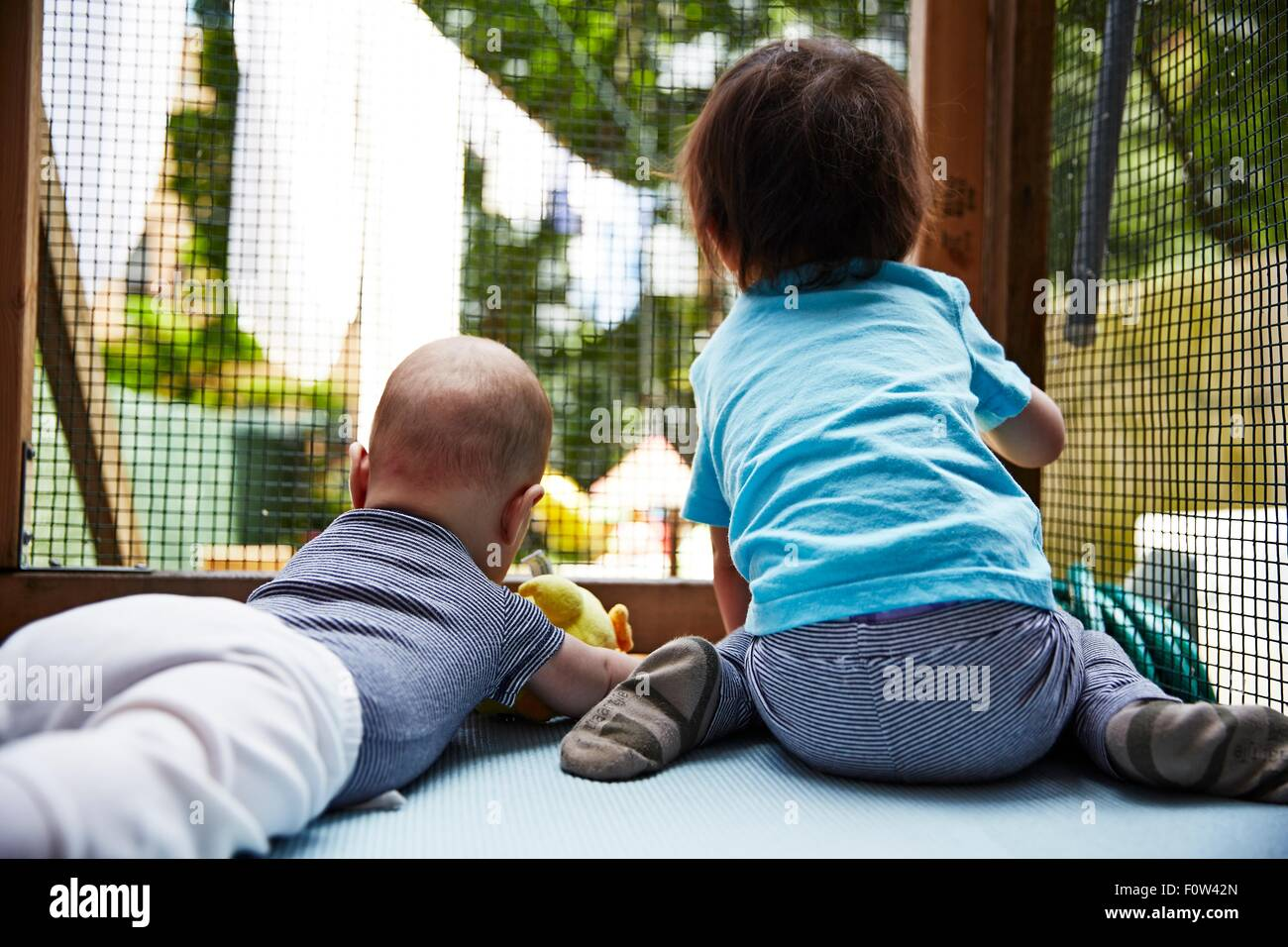 Brothers playing inside playpen - Stock Image