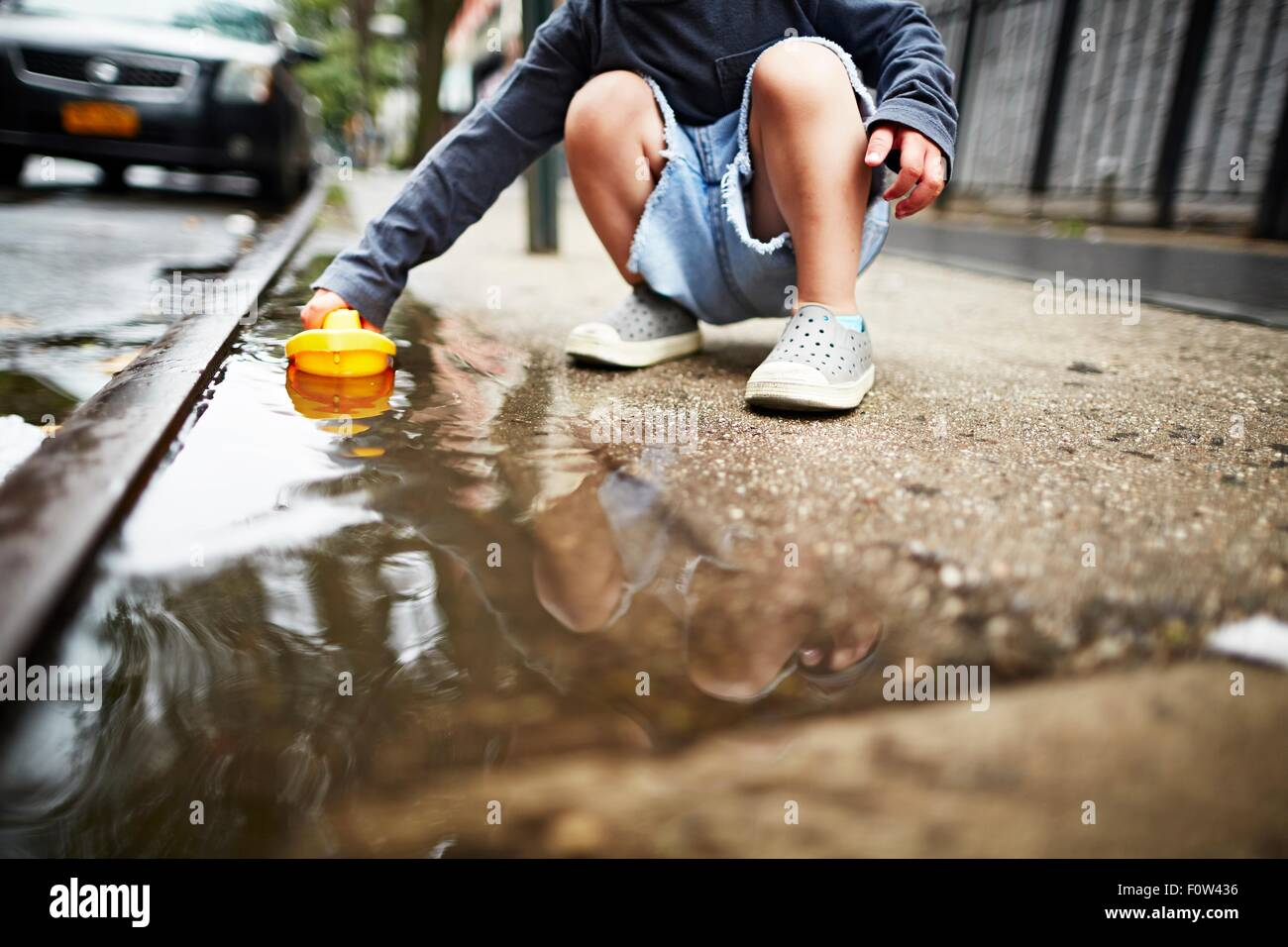 Boy playing with toy boat on water on pavement - Stock Image