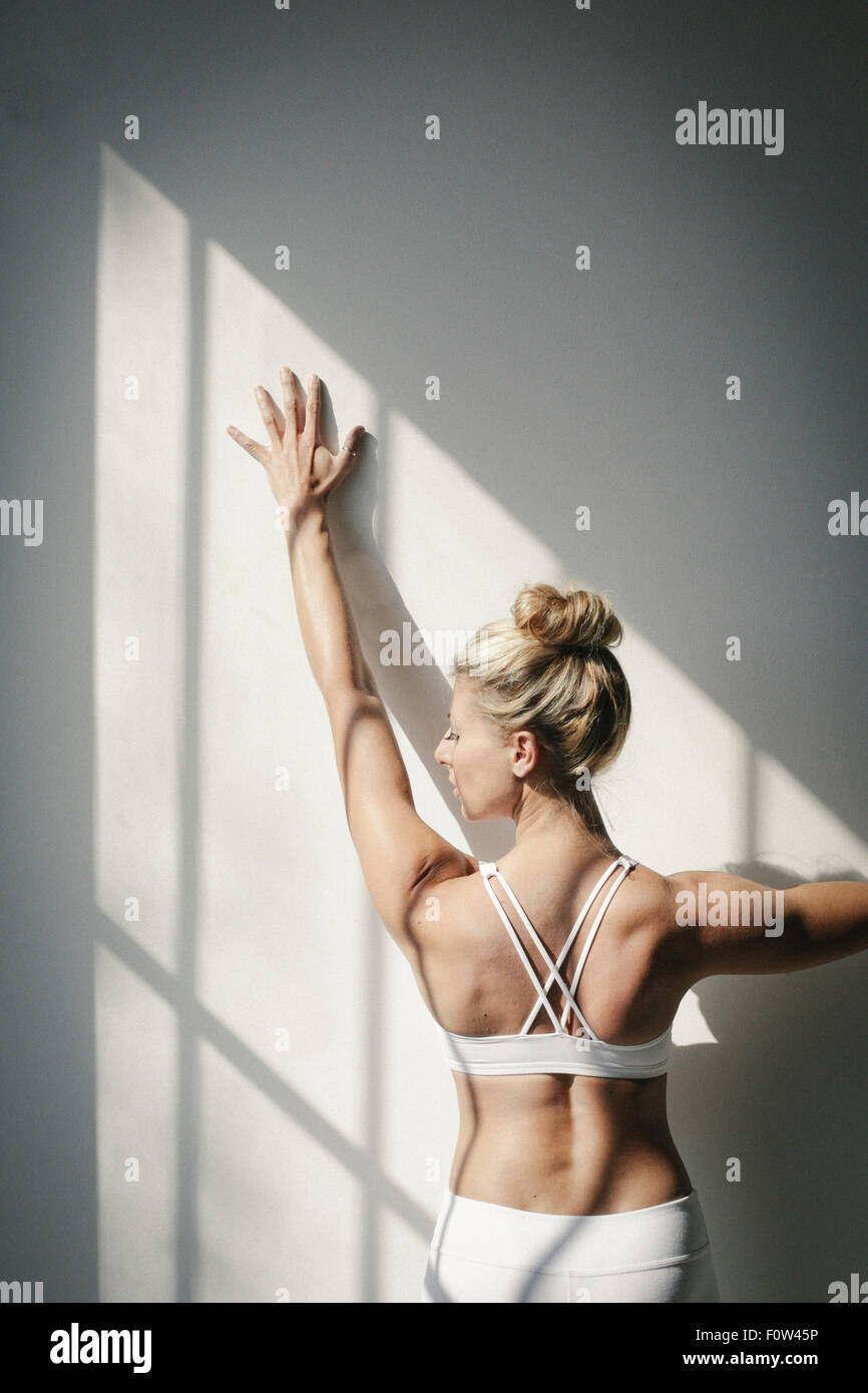 A blonde woman standing in front of a white wall, doing yoga, her arm raised, touching the wall. - Stock Image