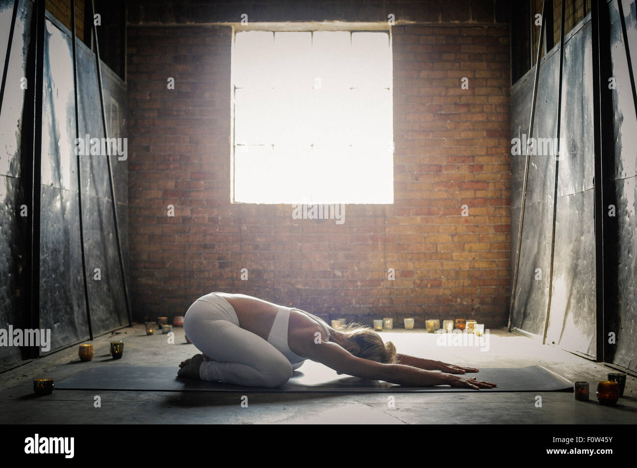 A blonde woman, in a white crop top and leggings,lying on a yoga mat on the floor surrounded by candles, arms outstretched - Stock Image