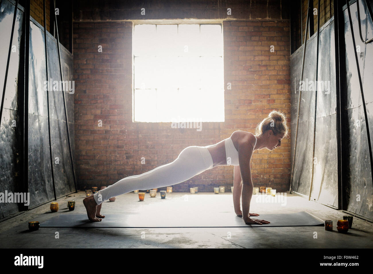 A blonde woman, in a white crop top and leggings, bending down on the floor surrounded by candles, doing yoga. - Stock Image