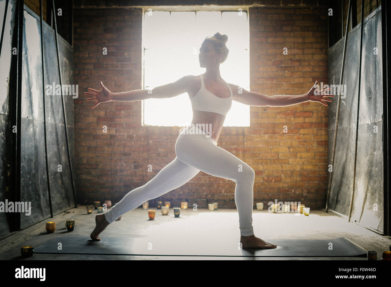 A blonde woman standing on a yoga mat surrounded by candles, doing yoga, her arms outstretched. - Stock Image