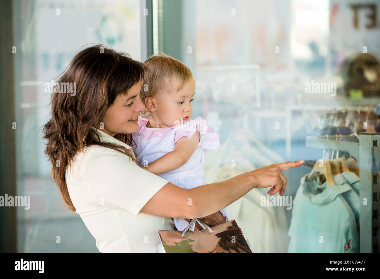 Mother with little girl in white dress looking through shop window - Stock Image