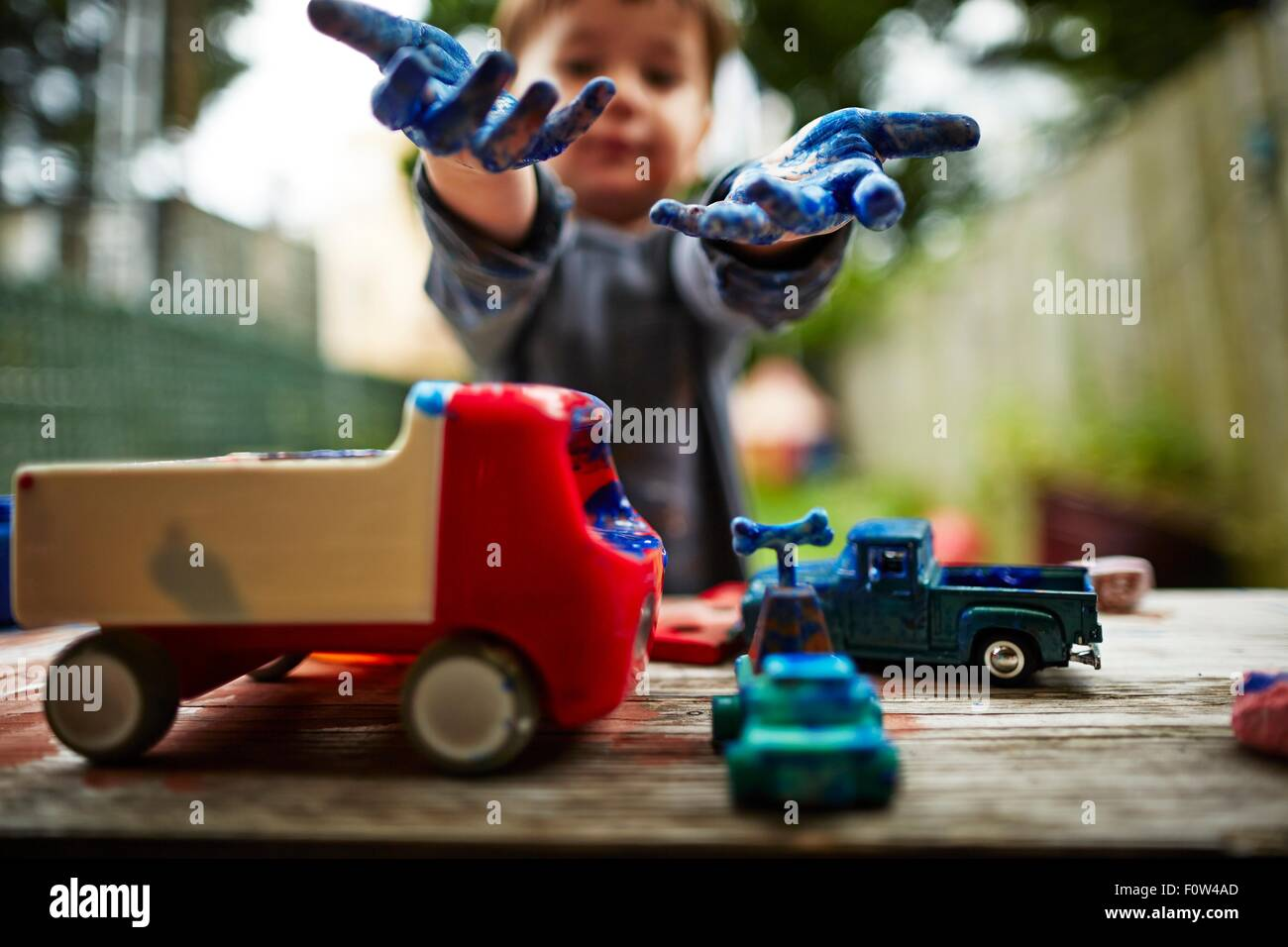 Boy playing with toy trucks and watercolour - Stock Image