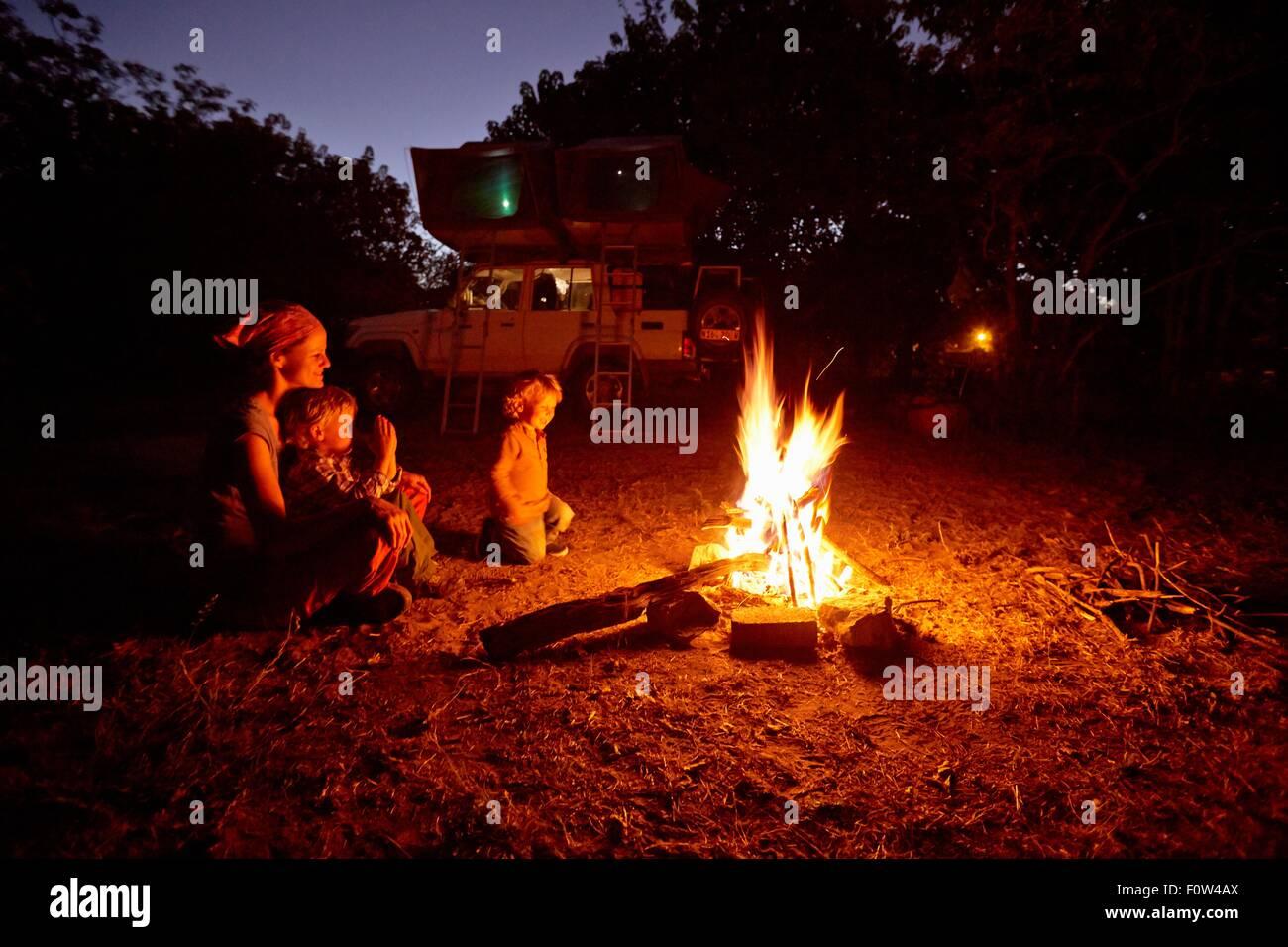 Mother and sons by campfire, Nxai Pan National Park, Kalahari Desert, Africa - Stock Image