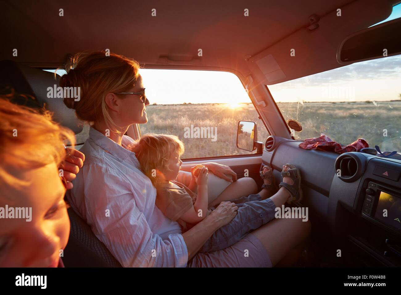 Mother and sons travelling in vehicle, Nxai Pan National Park, Kalahari Desert, Africa - Stock Image
