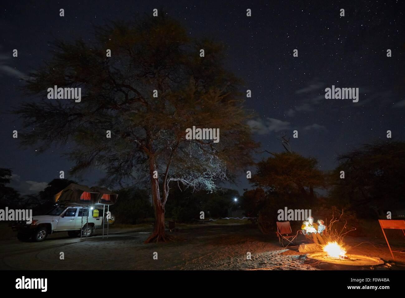 Family by campfire, Nxai Pan National Park, Kalahari Desert, Africa - Stock Image