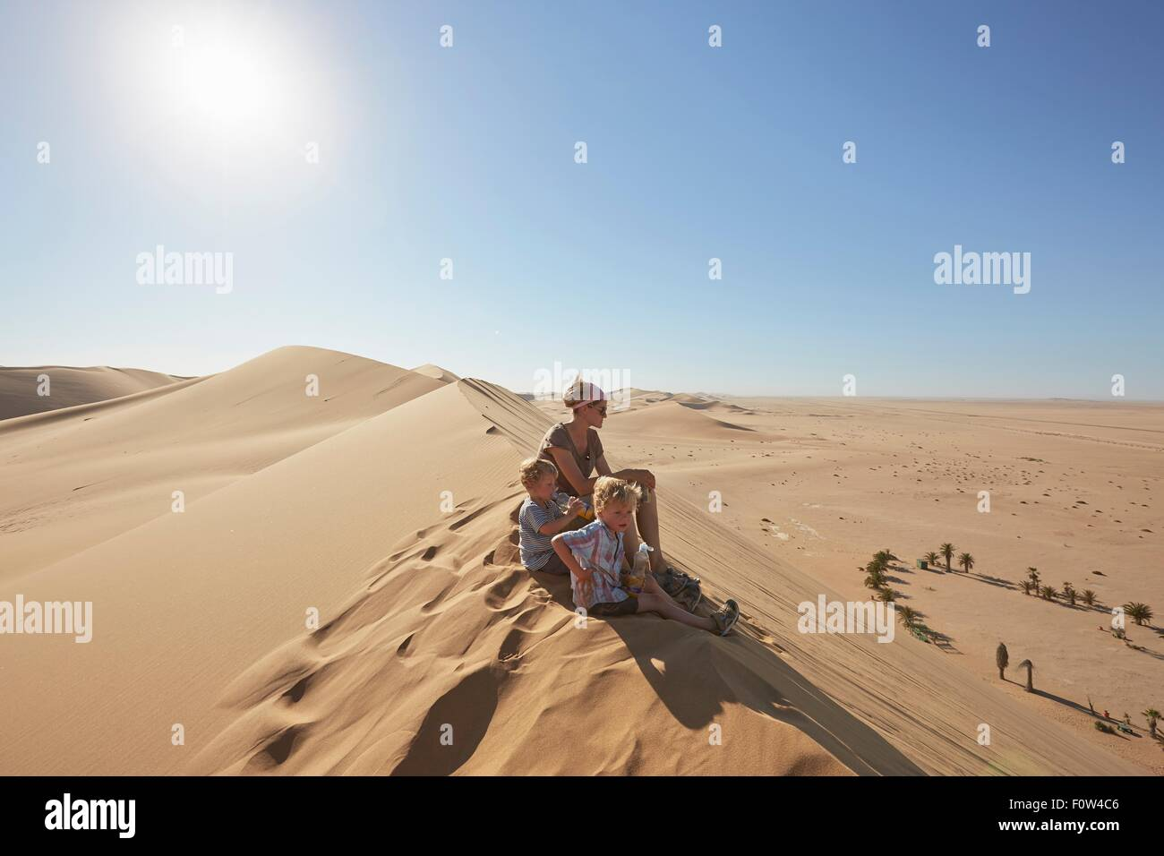 Mother and sons sitting on sand dune, Dune 7, Namib-Naukluft National Park, Africa Stock Photo
