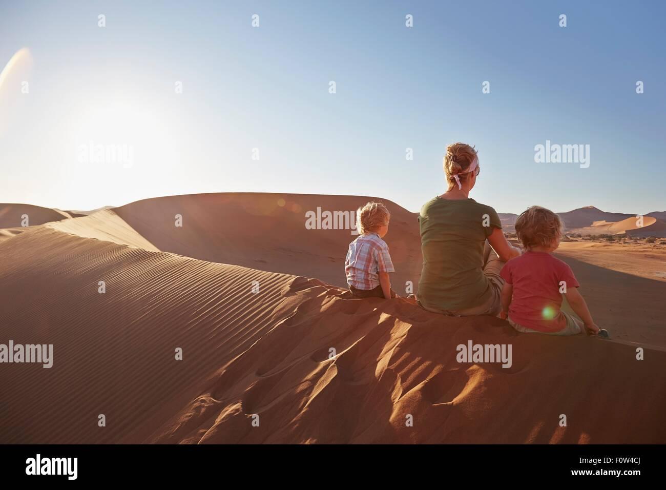 Mother and sons sitting on sand dune, Namib Naukluft National Park, Namib Desert, Sossusvlei, Dead Vlei, Africa - Stock Image