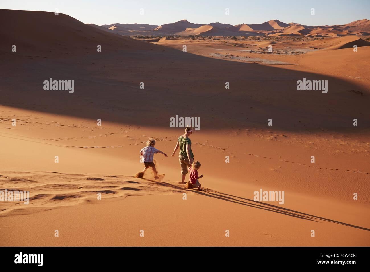Mother and sons walking on sand dune, Namib Naukluft National Park, Namib Desert, Sossusvlei, Dead Vlei, Africa - Stock Image